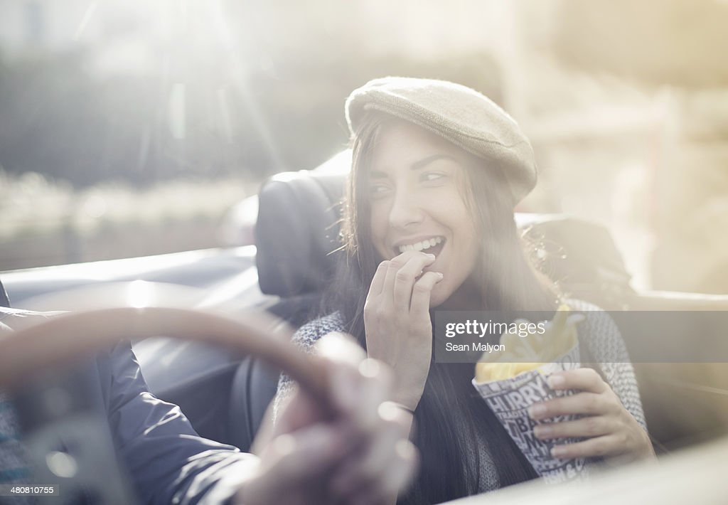 Young couple in convertible, woman eating chips