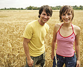 Young couple in cornfield, smiling, portrait