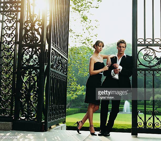 Young Couple in Evening Wear Leaning on a Wrought Iron Gate