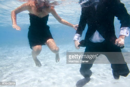 Young couple in evening-wear floating in the ocean : Stock Photo