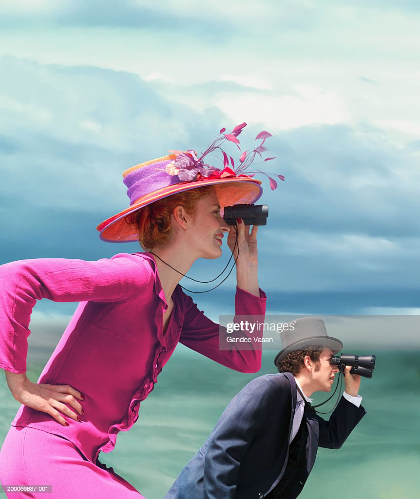 Young couple in formal wear looking through binoculars outdoors