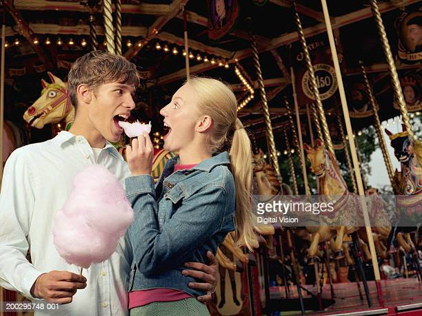 Young couple in front of carousel, woman feeding man candy floss