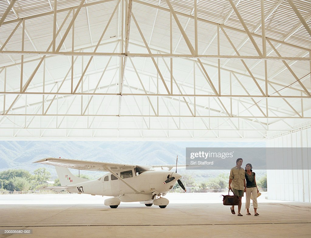 Young couple in hangar, private plane in background