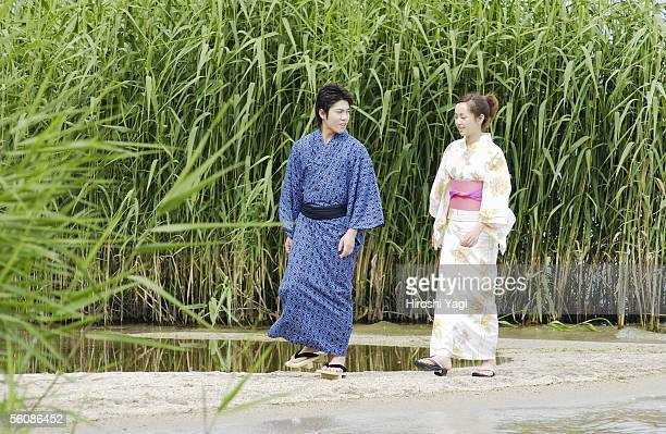 A young couple in kimono walking on lake side