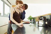Young couple in kitchen, man feeding woman blueberry, smiling