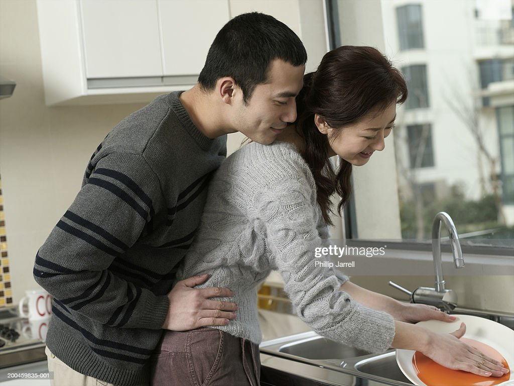 Young woman washing dishes in kitchen by andersen ross photography for - Young Couple In Kitchen Man Standing Behind Woman Washing Dishes Stock Photo