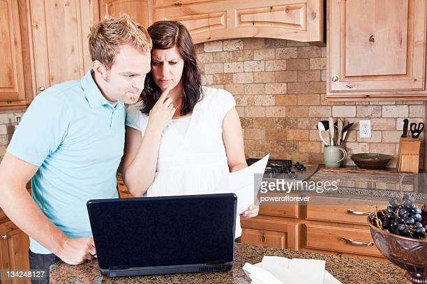 Young Couple in Kitchen Paying Bills Online