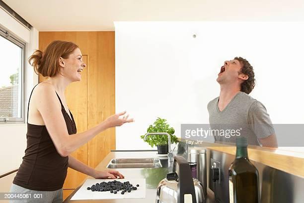 Jeune couple dans la cuisine, femme jeter de cassis pour homme