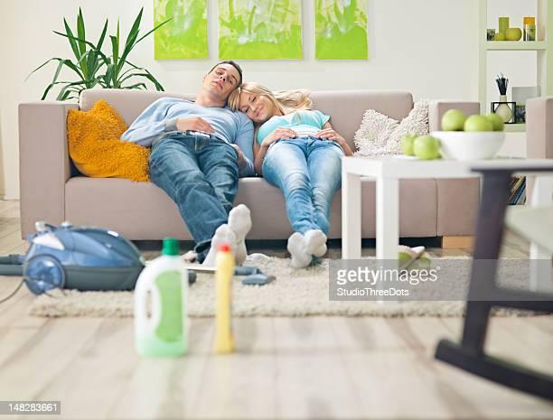 Jeune couple dans la salle de séjour reposant sur un canapé