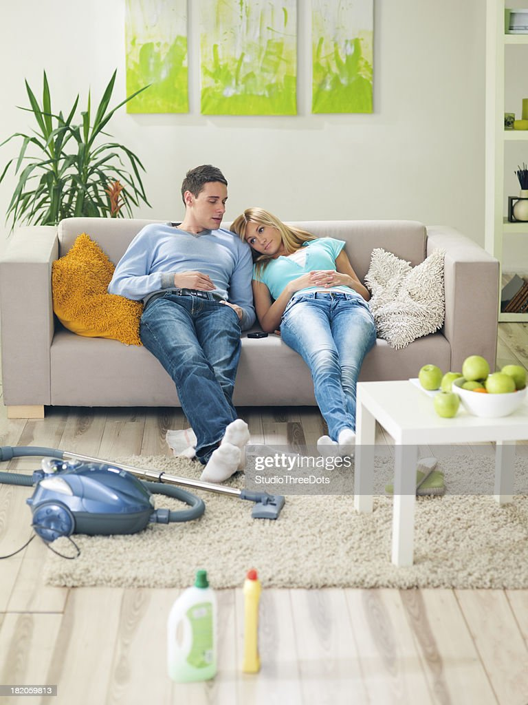 young couple in living room resting on sofa : Stock Photo