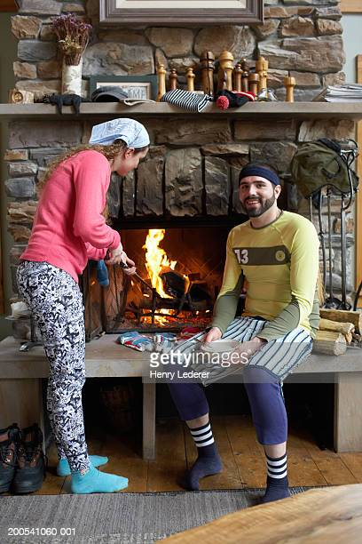 Young couple in lodge by fireplace, woman poking fire