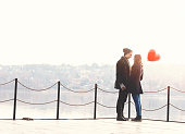Young couple in love, at the riverside, with a red balloon