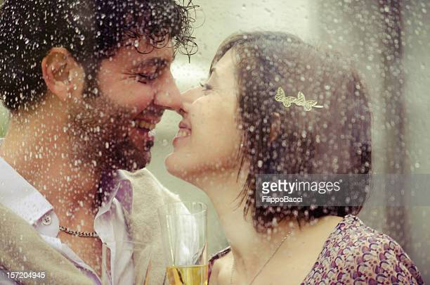 Young couple in love behind a wet window drinking champagne