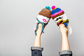 Funny woman legs with funny couple wearing knitted hats and scarfs