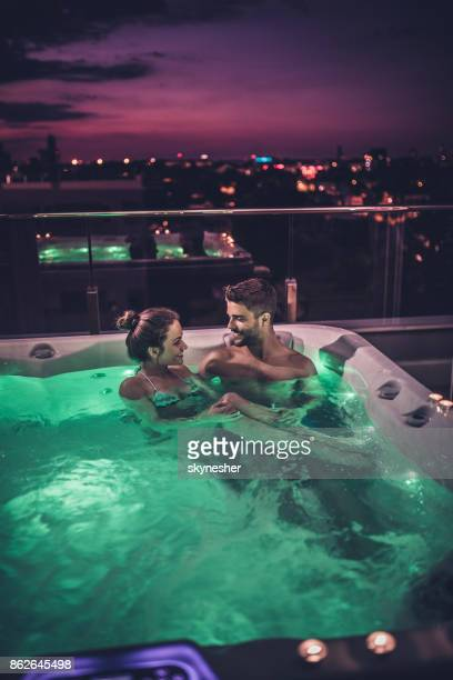 Young couple in love enjoying in romantic evening in a jacuzzi.
