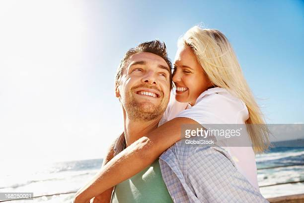 Young couple in love hugging on a sunny beach