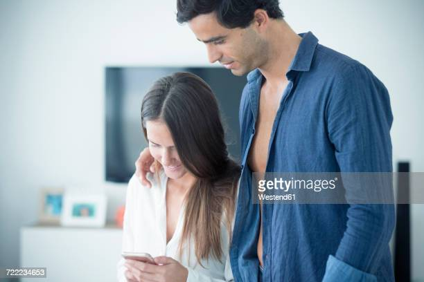 Young couple in love looking at cell phone at home