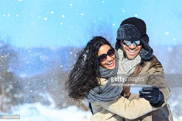 Young couple in love making selfie on the snow
