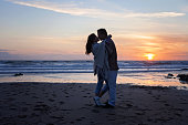 Young couple in love on the ocean on sunset
