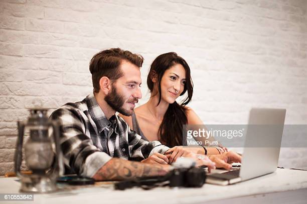 Young couple in love planning a trip with laptop