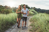 Outdoor shot of young couple in love walking on pathway through grass field. Man and woman walking along tall grass field.