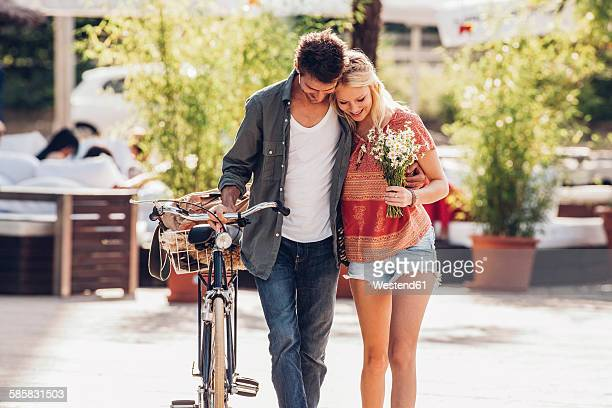 Young couple in love with bicycle and bunch of flowers