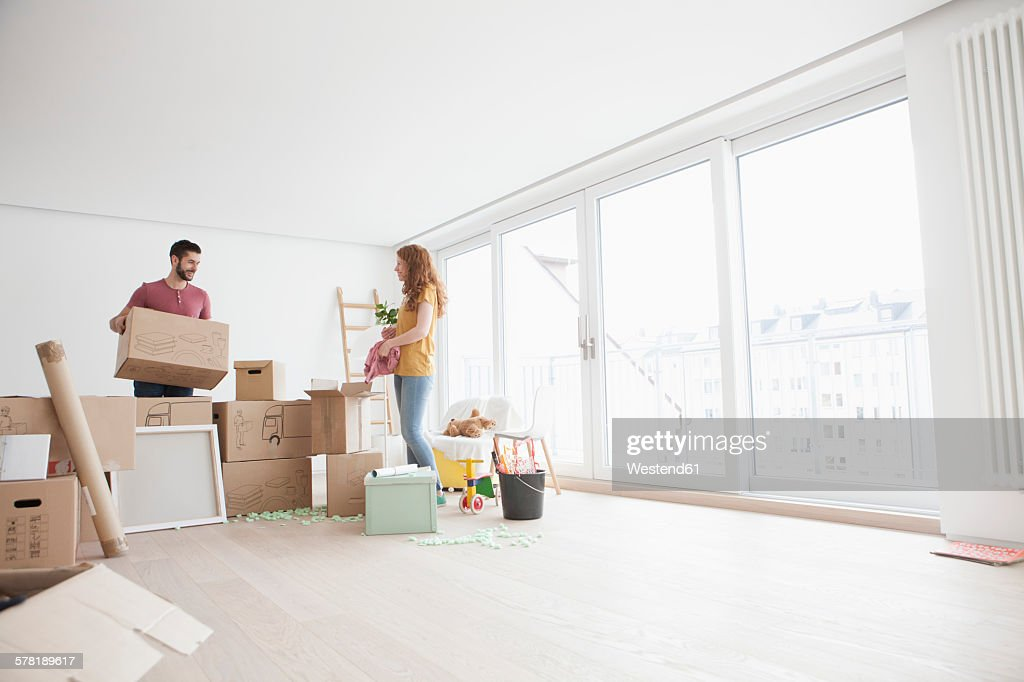 Young couple in new flat unpacking cardboard boxes