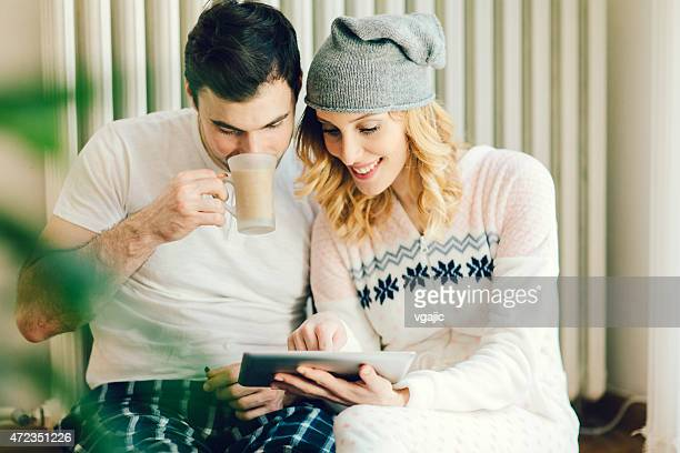 Young Couple In Pajamas Using Digital Tablet.