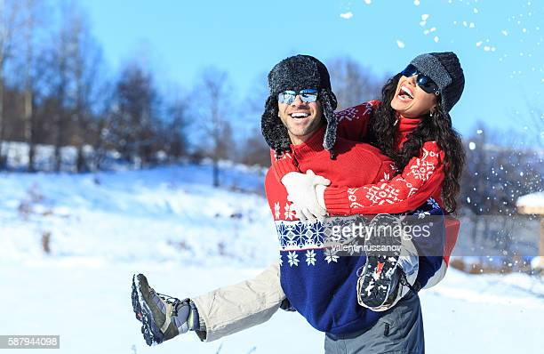Young couple in piggyback ride on the snow mountain
