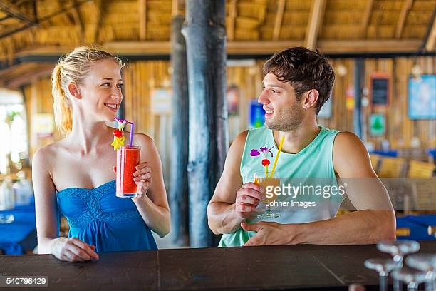 Young couple in restaurant having cocktails