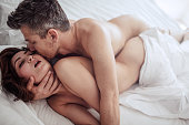 Sensual young couple making love in bedroom. Romantic man and woman having intimate sex in bed