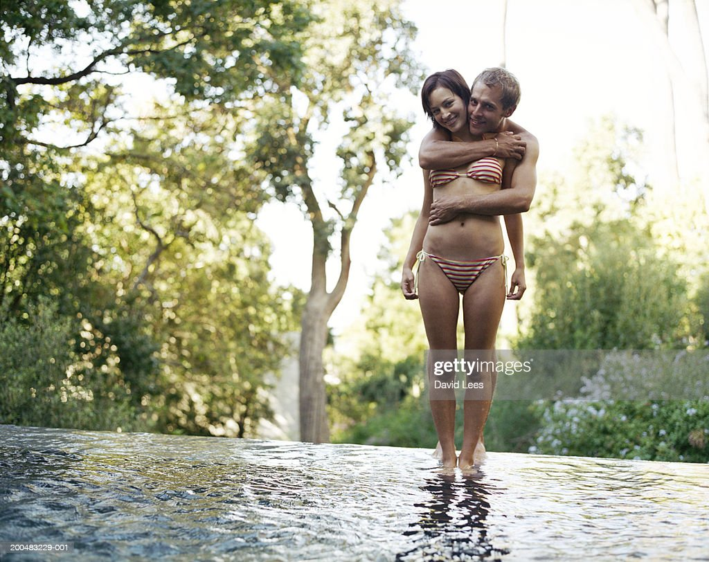 Young couple in swimwear embracing in shallow water : Foto stock