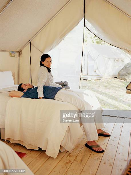 Young couple in tent, man lying on bed