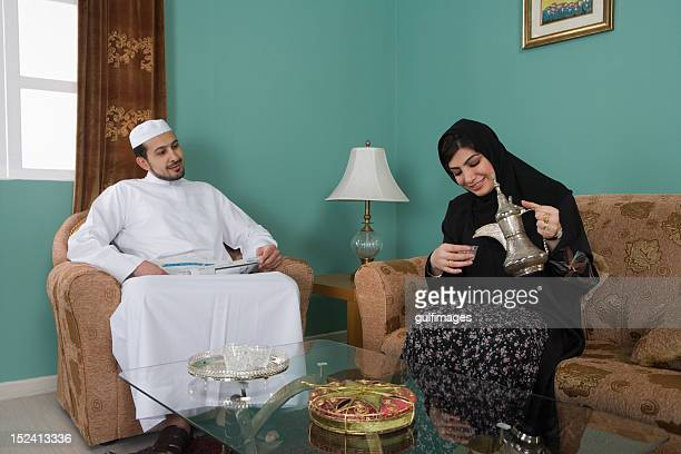 Young couple in the living room, woman serving tea