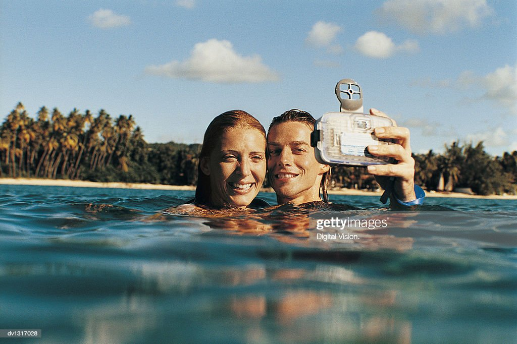 Young Couple in the Sea Photographing Themselves
