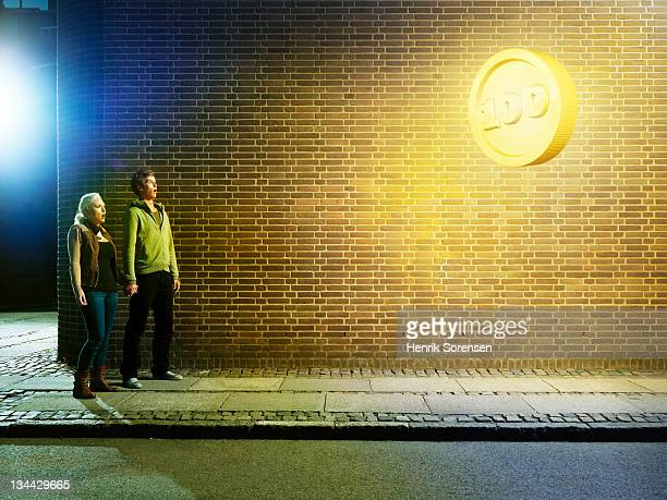 young couple in the street, looking up at coin
