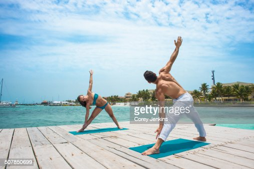 Young couple in triangle pose on pier, San Pedro, Belize