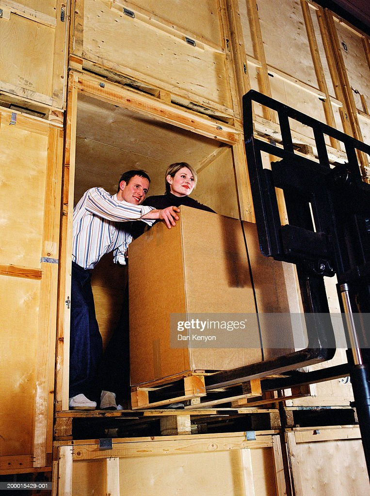 Young couple in warehouse loading box onto forklift : Stock Photo