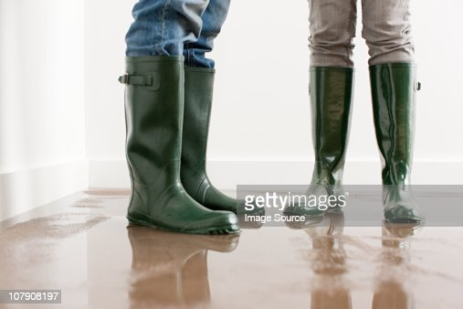 Young couple in wellington boots on flooded floor