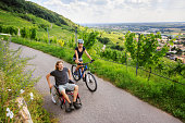 Young couple enjoying time outdoors. She is cycling, he is sitting in a wheelchair.