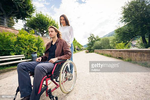 Young couple in wheelchair strolling in the park