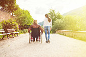 Young couple in wheelchair strolling in a park along the banks of the river Neckar in Heidelberg, Germany.