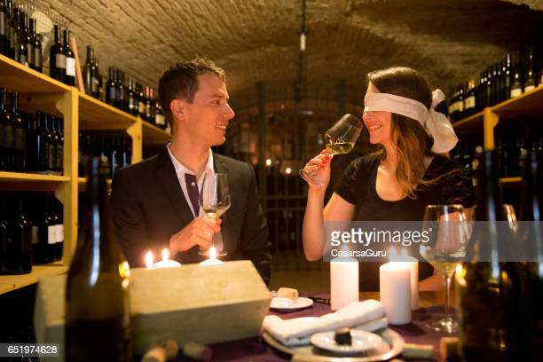 Young Couple In Wine CellarTasting Wine Blindfold