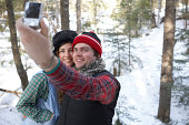 Young couple in woods taking digital self portrait, winter
