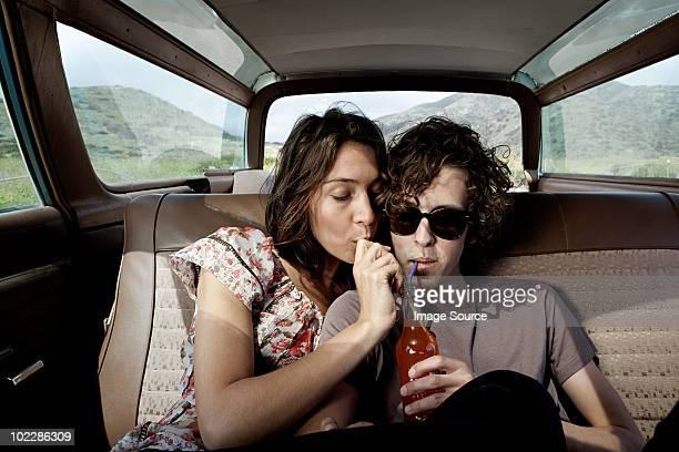 Junges Paar im Auto trinken Cola
