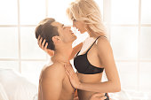 Young couple man and woman intimate relationship on bed kissing