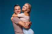 Young couple is hugging on blue background in studio. They wear T-shirts, jeans and smile. Friendship, love and relationships concept
