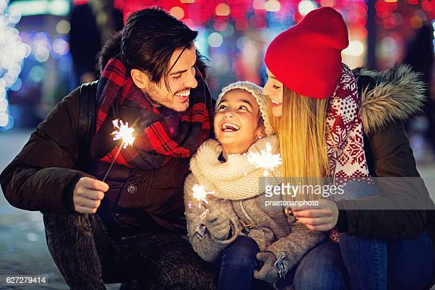 Young couple is hugging their daughter at Xmas