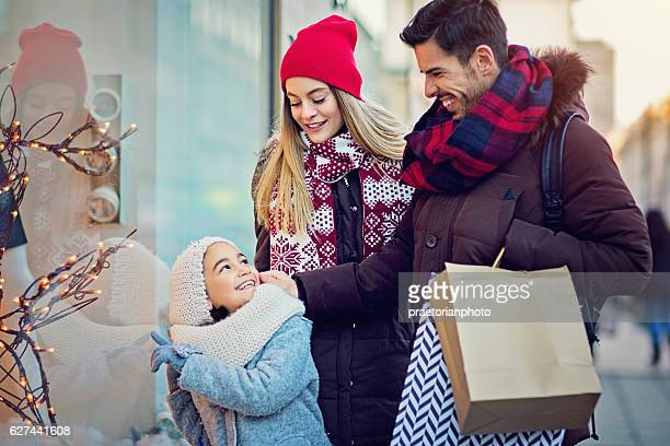 Young couple is looking in the shop window at Xmas