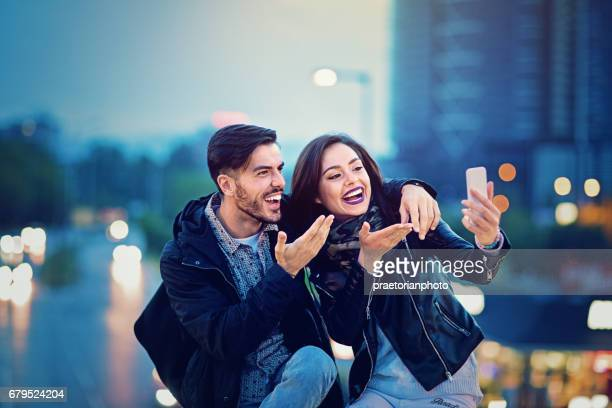 Young couple is making videocall on the bridge in the night